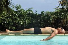 Relax at swimming pool. A man relaxed near swimming pool Royalty Free Stock Photography