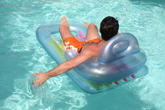 Relax In The Swimming Pool. Lifestyles - Man relaxing on inflatable mat in the swimming pool Stock Photo