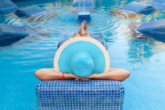 Relax on swimming pool bed. Woman in hat relaxing on swimming pool bed Stock Photography