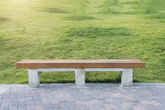 Relax and take a rest concept. Wood chesterfield with bricks flo. Or and green grass in park or garden. Advertising background.  Picture for add text message Royalty Free Stock Images