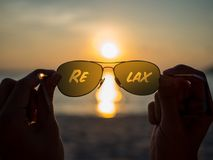 Relax text on eye glasses. On sunset beach, travel and beach background concept Royalty Free Stock Images