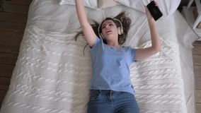 Relax time, joyful girl into headphones falls on bed and listens to songs from smartphone and enjoying music while. Resting at home on leisure stock footage