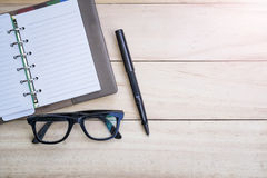 Relax time. Top view blank notebook with glasses and black pen on desk, wooden table royalty free stock photos