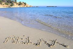 Relax on a tropical beach. Relax written in the sand on the beach with clear sea Stock Image