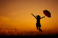 Relax Umbrella woman jumping and sunset silhouette Stock Images