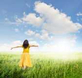 Relax Woman in green  fields with blue sky Royalty Free Stock Photography