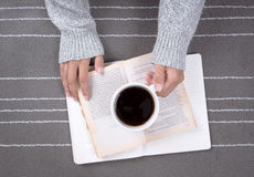 Relax woman hand holding coffee cup of hot drink and read a book Royalty Free Stock Image
