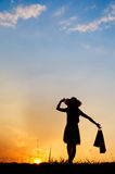 Relax Woman holding shopping bags in sunset silhouette Royalty Free Stock Photo