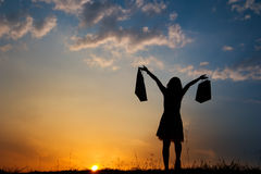 Relax Woman holding shopping bags in sunset silhouette Royalty Free Stock Photos
