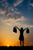 Relax Woman holding shopping bags in sunset silhouette Stock Photos