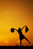 Relax Woman holding shopping bags in sunset silhouette Stock Images