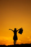 Relax Woman holding shopping bags in sunset silhouette Stock Image