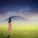 Relax woman look up to the star and standing on Green grass fields big mountain and Star night Royalty Free Stock Photo