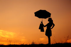Relax Woman and shopping bags in sunset silhou Stock Photo