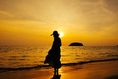 Relax Woman standing  on the beach  sea  Sunset silhouette royalty free stock photography