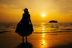 Relax Woman standing  on the beach  sea  Sunset silhouette stock photography