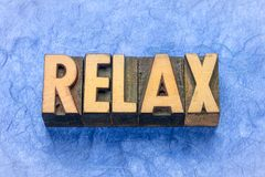 Relax word abstract in wood type. Relax word abstract in vintage letterpress wood type against handmade textured paper stock images
