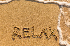 Relax - word drawn on the sand beach. With the soft wave stock images