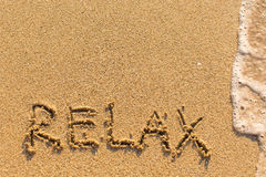 Relax - word drawn on the sand beach. With the soft wave royalty free stock photo