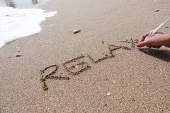 Relax word handwritten on beach sand with white feather on summer time royalty free stock photography