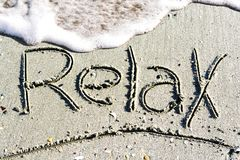 Relax word handwritten on sand, on the beach. Relax word handwritten on sand, near the sea royalty free stock image