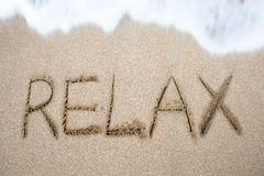 Relax word handwritten in sand on beach. With white wave foam stock photography
