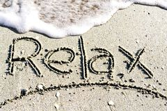 Relax word handwritten on sand, near the sea. Relax word handwritten on sand stock photography