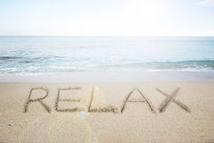Relax word handwritten in sand on sunny beach Stock Photos