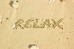 Relax word handwritten on sand Royalty Free Stock Images