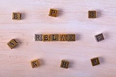 Relax word metal block. Relax word gold and silver metal block on white wood with letter blocks around stock images