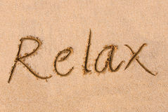 Relax word on sand. The word 'Relax' written out on a sandy beach royalty free stock image