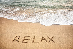 Relax word on the sand. Beach near the ocean royalty free stock photo