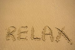 Relax word on sand beach texture. Natural sand background for design. Summer concept. Relax word on sand beach texture. Natural sand background for design stock photos