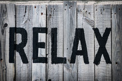 Relax. The word relax stencilled on weathered wood in black Royalty Free Stock Photo