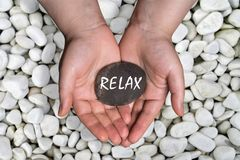 Relax word in stone on hand. A woman holding black stone with relax word by hand on white river stones royalty free stock photography