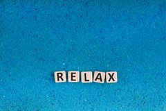 Relax word on stone. Relax word write in square white stone on blue sand, free space for your text stock photography