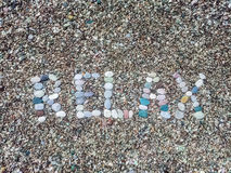 Relax word from stones on pebble beach Stock Photography