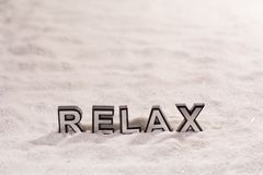 Relax word on white sand. Relax word silver and black on shiny white sand stock photography