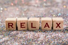 Relax word. Wood Cubes Relax word on glitter background stock photos