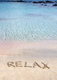 Relax word written in the sand, on a beautiful beach with clear blue waves in background Stock Photo