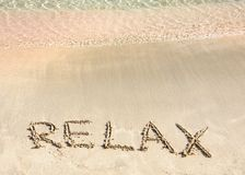 Relax word written in the sand, on a beautiful beach with clear blue waves in background Stock Image