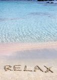 Relax word written in the sand, on a beautiful beach with clear blue waves in background Stock Photography