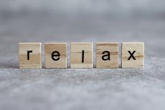 Relax word written on wood cube. With gray background stock images