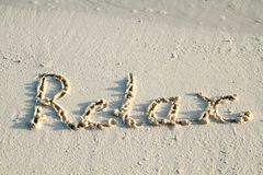 'Relax' written in sand. Royalty Free Stock Photos