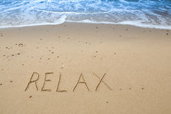 Relax. Written in the sand at the beach Royalty Free Stock Photos