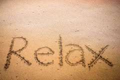 Relax written into the sand on a beach royalty free stock photography