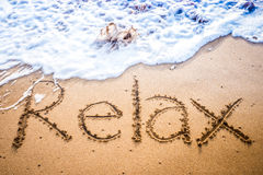 Relax written into the sand on a beach Stock Photography