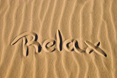 Relax written in the sand. The word relax written on a sunny beach Royalty Free Stock Image