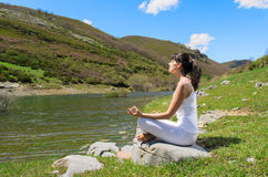 Relax and Yoga Outdoors. Young woman practices yoga and relax in nature Royalty Free Stock Photos