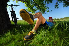 Relax. Young lady relaxing on a green meadow after cycling. Focus on a face Stock Image
